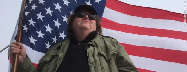 Michael Moore posiert mit der Flagge der USA in der Hand.